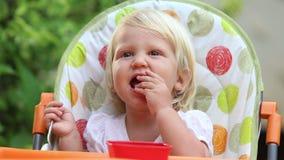 La niña se sienta en silla y come la sonrisa del mango metrajes