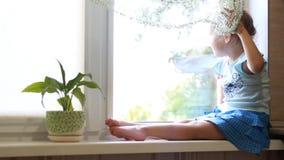 La niña se sienta en un travesaño de la ventana y mira hacia fuera la ventana El concepto de expectativa