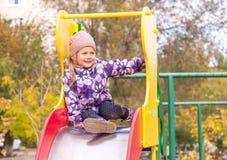 La niña se sienta en una diapositiva en la yarda Fotos de archivo