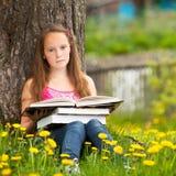 La niña se sienta en una hierba mientras que lee un libro Imágenes de archivo libres de regalías