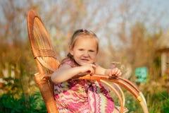 La niña se sienta en una silla Imagen de archivo libre de regalías