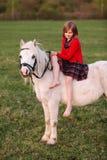 La niña se sienta a horcajadas en un caballo blanco y la mirada abajo Fotos de archivo libres de regalías
