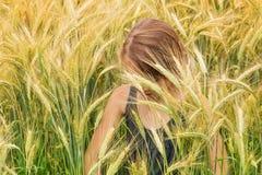La niña se sumergió bajo puntos de un campo de grano de maduración fotografía de archivo libre de regalías