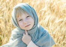 La niña se vistió en campo de trigo gris de lin del pañuelo en verano 5 años tristes mordidos primer del niño Foto de archivo