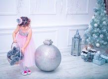 La niña se vistió en el vestido hermoso de la flor blanca de la moda que presentaba cerca del árbol de navidad Imagenes de archivo