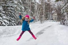 La niña se vistió en una capa azul y un sombrero rosado y las botas, bosque del invierno de los saltos de altura Fotos de archivo libres de regalías