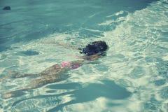 La niña se zambulle en la piscina Imagen de archivo libre de regalías
