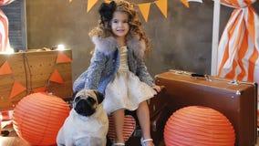 La niña sienta en retro una maleta con el perro metrajes