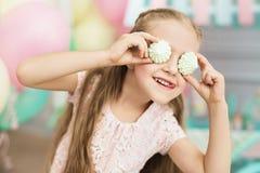 La niña sonríe y pone las tortas sobre sus ojos Foto de archivo