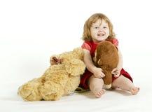 La niña sonriente con los juguetes de la felpa. Fotografía de archivo