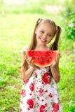 La niña sonriente con los ojos azules come una rebanada de sandía Imagenes de archivo