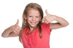 La niña sonriente detiene sus pulgares Fotos de archivo libres de regalías