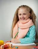 La niña sonriente dibuja en la tabla, cerca del inhalador en gris Fotografía de archivo