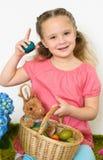 La niña sonriente juega con una cesta de huevos de Pascua Imagen de archivo libre de regalías