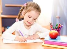 La niña sonriente linda está escribiendo en el escritorio Fotografía de archivo