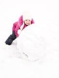 La niña sonriente linda hace el muñeco de nieve en día de invierno Imagen de archivo