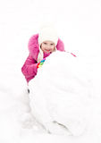 La niña sonriente linda hace el muñeco de nieve en día de invierno Imágenes de archivo libres de regalías