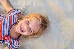 La niña sonriente miente en la arena de la playa Foto de archivo