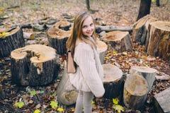 La niña sonriente se coloca al lado de tocones de madera en el bosque en el día del otoño Imagen de archivo