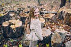 La niña sonriente se coloca al lado de tocones de madera en el bosque en el día del otoño Foto de archivo