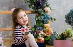 La niña sonriente se está sentando cerca de las escaleras y del flowe de madera Fotos de archivo libres de regalías