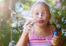 La niña sopla burbujas de jabón al aire libre Imágenes de archivo libres de regalías