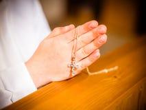 La niña sostiene la cadena con la cruz fotos de archivo libres de regalías