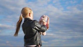 La niña sostiene el juguete grande del conejito de la felpa Conejito hecho a mano del juguete de la materia textil adentro en la  metrajes
