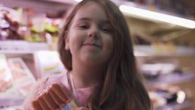 La niña sostiene las salchichas en la tienda y las demostraciones manosean con los dedos para arriba almacen de metraje de vídeo