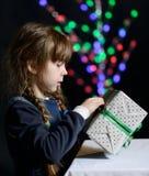 La niña sostiene una caja con un regalo disponible y la abre Imágenes de archivo libres de regalías