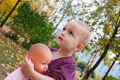 La niña sostiene una muñeca Imagenes de archivo