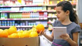 La niña sostiene una tableta en el mercado de la tienda elige la naranja de la fruta almacen de metraje de vídeo