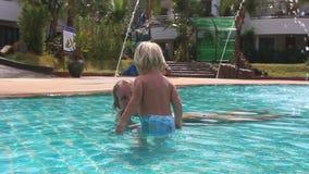 La niña sube para mimar en piscina y tira de la mano almacen de video
