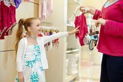 La niña toma la decisión entre dos trajes de baño Imagenes de archivo