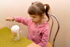La niña toma un cóctel del oxígeno de la cuchara Phytobar del niño Foto de archivo