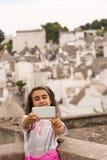 La niña toma un selfie delante del trulli de Alberobello fotografía de archivo libre de regalías