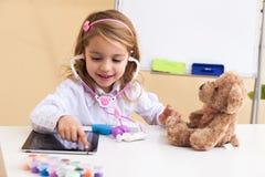 La niña trata un oso del juguete imagenes de archivo