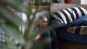 La niña triste abraza ansiedad que se sienta de la muñeca en la esquina almacen de metraje de vídeo
