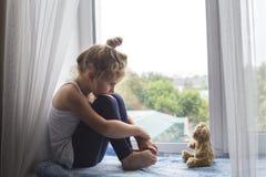 La niña triste se sienta en un travesaño de la ventana y mira un oso imagenes de archivo