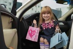 La niña va a hacer compras en un coche Foto de archivo