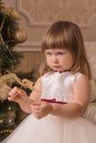 La niña vacila mantener un juguete del ` s del Año Nuevo sus manos fotografía de archivo