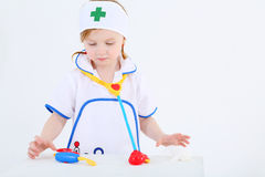 La niña vestida como enfermera juega con los instrumentos médicos del juguete foto de archivo