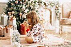 La niña vestida en pijama sienta o la alfombra y bebe un co fotos de archivo libres de regalías