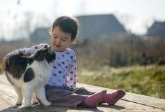La niña y el gato juegan fuera cerca de la casa Imagen de archivo libre de regalías