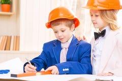 La niña y el muchacho están trabajando con los papeles de construcción Foto de archivo