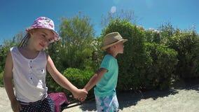 La niña y el muchacho van en el camino almacen de video