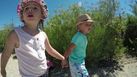 La niña y el muchacho van en el camino almacen de metraje de vídeo