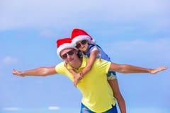 La niña y el padre feliz en Santa Hats gozan Foto de archivo