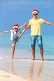 La niña y el papá feliz en Santa Hats disfrutan de vacaciones de la Navidad Foto de archivo