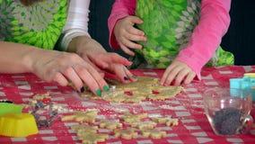 La niña y la mujer adulta da la fabricación de las galletas con las formas metálicas almacen de metraje de vídeo